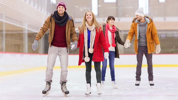 Deux couples d'amoureux sont en train de faire du patin à glace à la patinoire d'Odysseum.